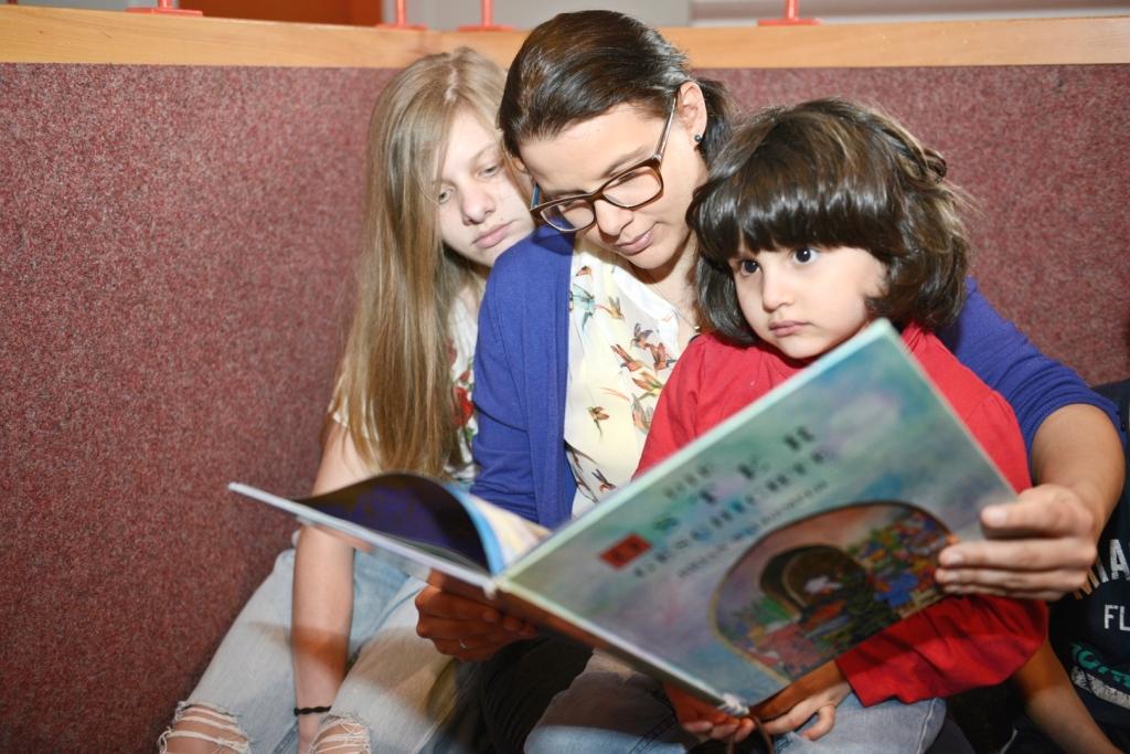 Eine junge Frau liest zwei Kindern vor, Foto: Marcus-Andreas Mohr