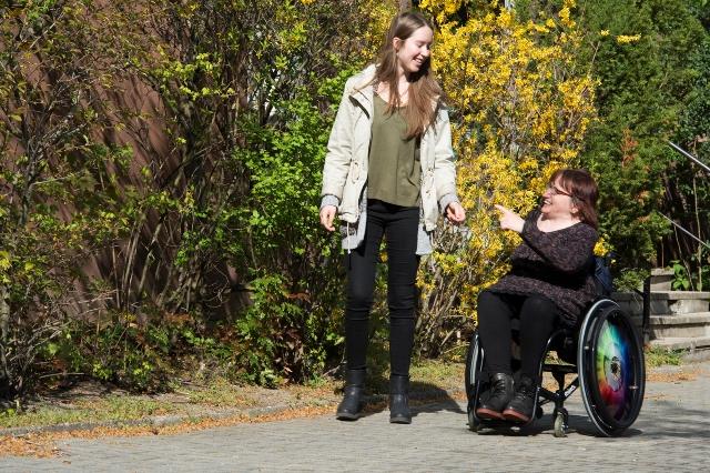Eine junge Frau und eine Frau im Rollstuhl unterhalten sich beim Spazieren gehen