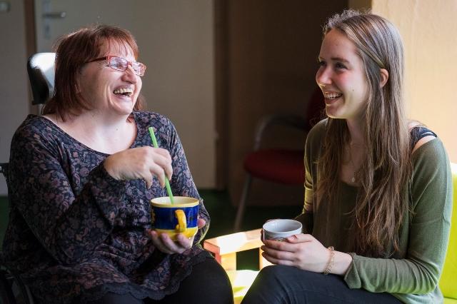 Eine junge Frau und eine Frau im Rollstuhl unterhalten sich