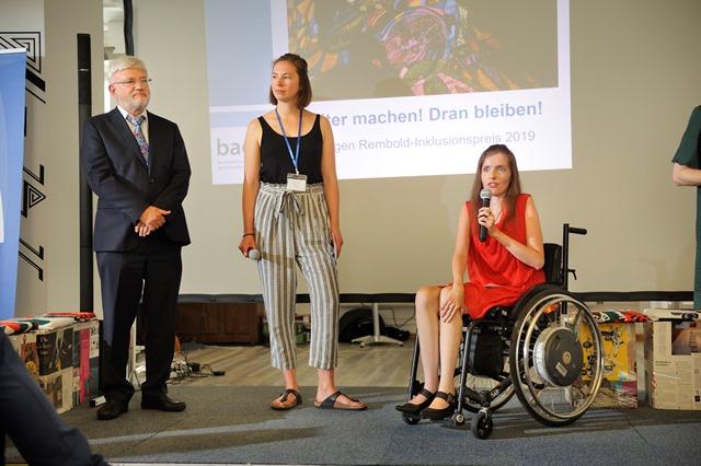 eine Frau im Rollstuhl redet mit Mikrofon, daneben noch eine junge Frau und ein älterer Herr